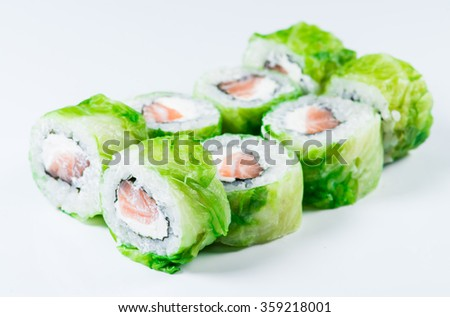 close-up of  Japan sushi roll with salmon and green lettuce (shallow DOF) on a white background - stock photo