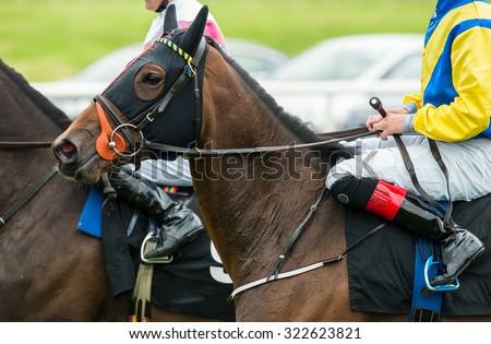 close up of jockeys on race horses - stock photo