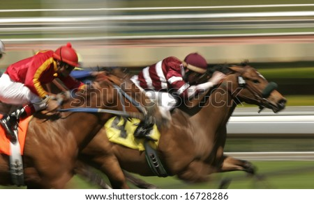 Close-up of Jockeys racing thoroughbreds. Shot at slow shutter speed to enhance motion effect.