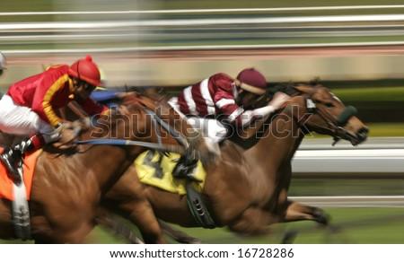 Close-up of Jockeys racing thoroughbreds. Shot at slow shutter speed to enhance motion effect. - stock photo