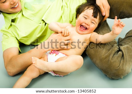Close-up of joyful child lying on the floor and laughing from tickling - stock photo