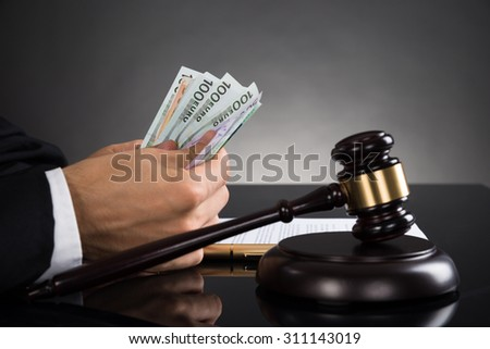 Close-up Of Judge Hands Counting Banknote In Front Of Gavel At Desk - stock photo