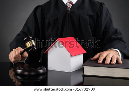 Close-up Of Judge Holding Gavel With House Model At Desk - stock photo