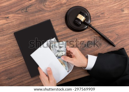 Close-up Of Judge Removing Money From Envelope In Courtroom - stock photo