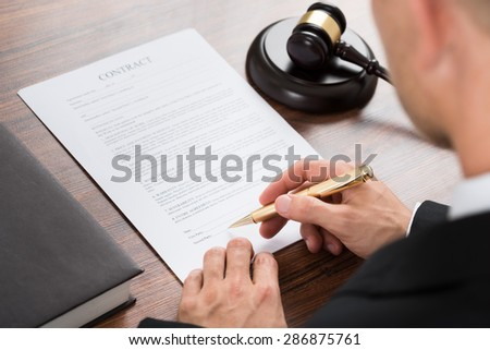 Close-up Of Judge Signing Contract Paper At Desk In Courthouse - stock photo