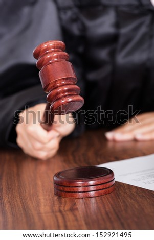 Close-up Of Judge Striking The Gavel In A Courtroom - stock photo