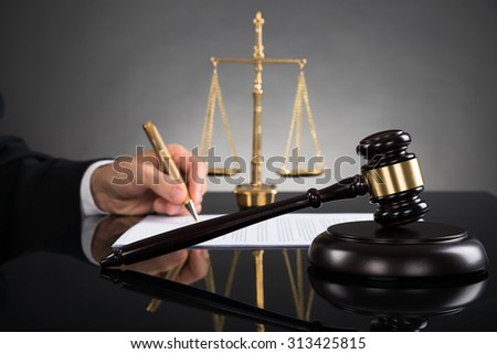 Close-up Of Judge Writing On Paper With Gavel And Scale At Desk - stock photo