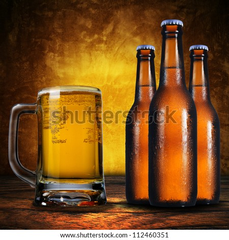 Close up of jug of beer and three beer bottles. Cold refreshment - stock photo