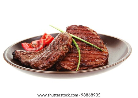 close-up of juicy sirloin beef with pasta tomatoes and green onion on dark dish isolated over white background - stock photo