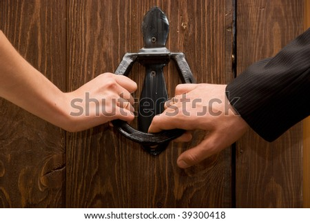 Close up of just married hands opening the door together