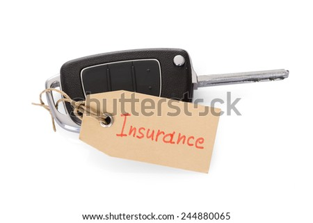 Close-up Of Key Attached With Insurance Tag On White Background - stock photo