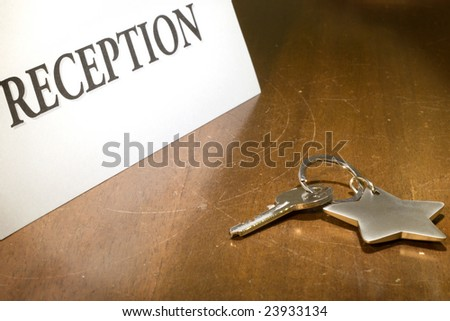 Close up of key on wooden reception desk - stock photo