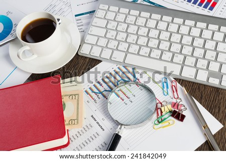 Close up of keyboard documents and coffee on office table - stock photo