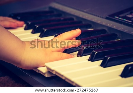 Close up of Keyboard of synthetizer. Music abstract background with hands of children playing on keyboard. - stock photo