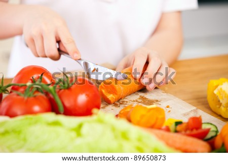 Close up of kid cutting vegetables for salad