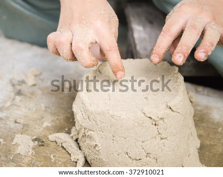 Close up of kid's hands playing sand