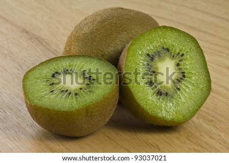 Close-up of 2 Kiwis with One Cut in Half on a Cutting Board - stock photo