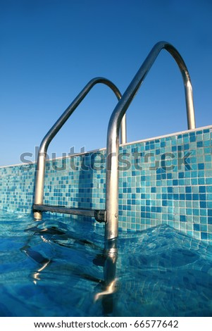 Close-up of ladder in swimming pool, summer day - stock photo