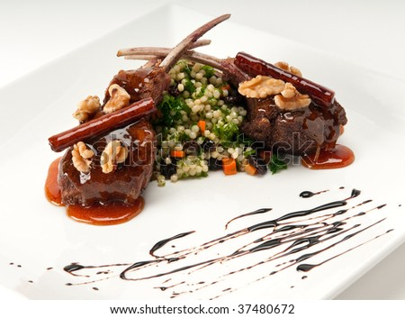 Close up of lamb chops with couscous and vegetables with a sauce of caramel, pepper and spices. - stock photo