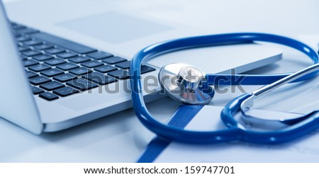 Close Up Of Laptop And Stethoscope On Desk - stock photo