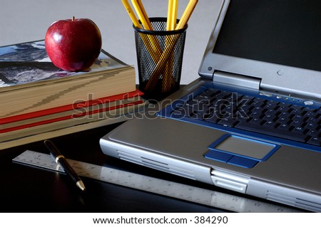Close-up of laptop, books, ruler, pen, pencils and apple on desk. Natural light hitting from the left.