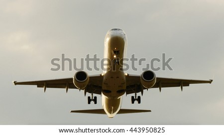 close up of large airplane flying over camera approaching airport for landing - stock photo