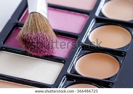 Close up of large cosmetic brush with pink blush dust sitting on palette of blush and skin cover up colors - stock photo
