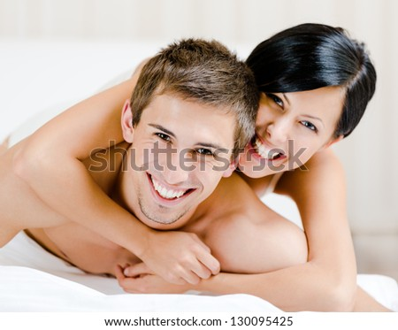 Close up of laughing couple who plays in bed. Woman lying on the back of the man  embraces him - stock photo