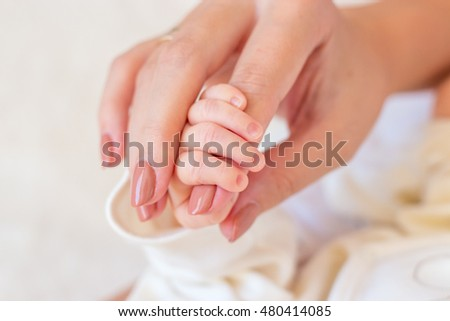 Close-up of legs, handles child. Happy mother kissing the feet, hands, fingers, the nose of the child. Gentle photo mom and baby.