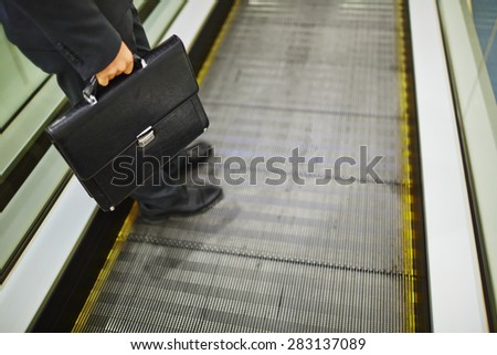 Close-up of legs of businessman with briefcase descending on escalator - stock photo