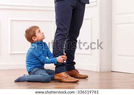 Close up of legs of man going to work. His son is asking him not to go. The child is sitting on flooring and gripping legs of his father. The boy is looking up with request - stock photo