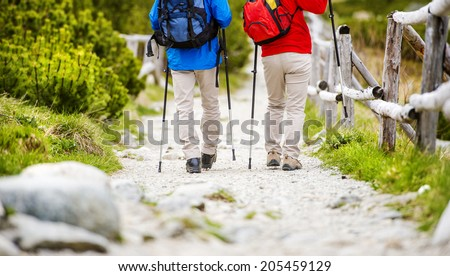 Close-up of legs of senior couple hiking at the beautiful mountains - stock photo