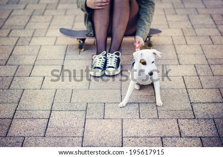 Close-up of legs of teenage girl on skateboard with her dog - stock photo