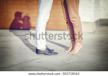 Close-up of legs of the kissing couple with shadows (cross processing filter ) - stock photo