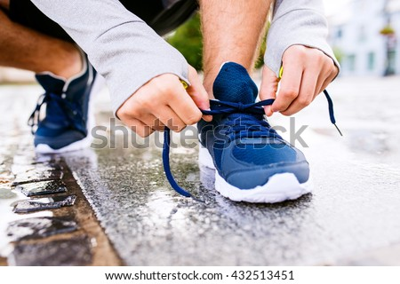 Close up of legs of unrecognizable runner, town, puddle - stock photo