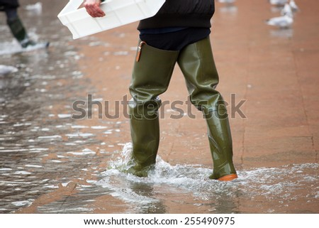 Close Up of legs with boots due to the high water. This flood happens when there is high tide in Venice, Italy. - stock photo