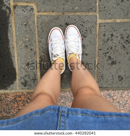 Close up of legs woman with dress jean and white sneakers outdoor great for any use. - stock photo