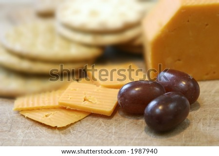 Close up of leicester red cheese and biscuits on wooden board and seedless red grapes. - stock photo