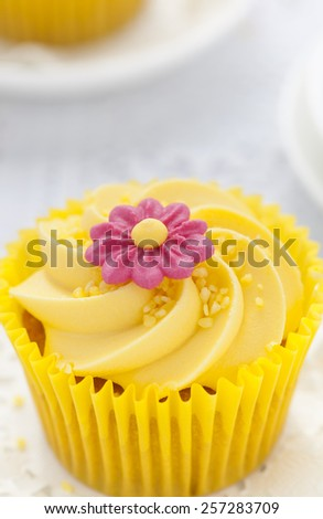 Close up of Lemon cupcake with butter cream swirl and fondant flower decorations - stock photo
