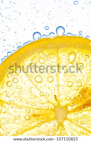 close-up of lemon slice in clear water with bubbles - stock photo