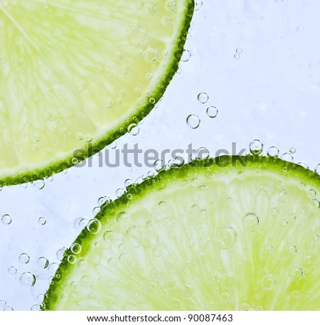 Close up of lime floating in bubbly water - stock photo