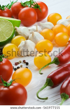 Close up of lime, fresh vegetables and spices on a white wooden background.