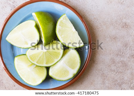 Close up of lime wedges on blue plate with copy space, view from above. - stock photo