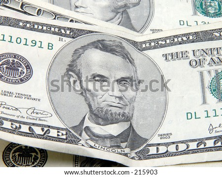 Close up of Lincoln on a five dollar bill suround by other bills