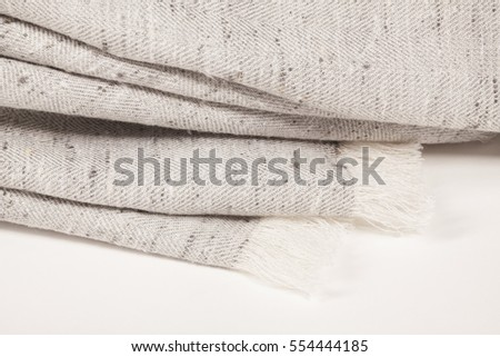 Close up of linen scarf with tassels on white background