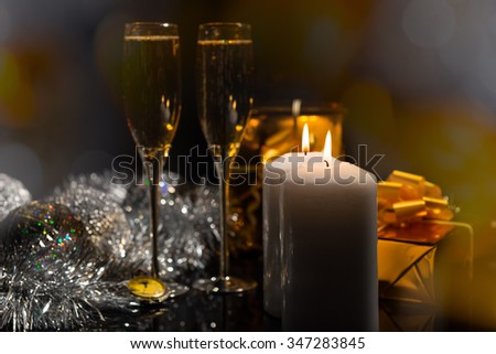 Close Up of Lit White Pillar Candles Casting Romantic Warm Glow on Festive Still Life of Champagne Glasses, Gold Wrapped Gifts, Pocket Watch and Silver Decorations