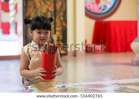 Close up of little asian girl hold Esiimsi ,Esiimsi is horoscope prediction equipment.