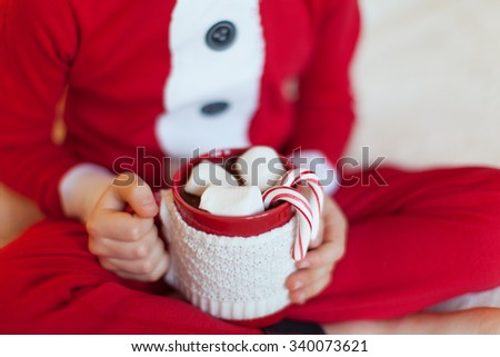 close-up of little boy in cozy pajamas holding cup with hot cocoa enjoying christmas time at home, shallow DOF - stock photo