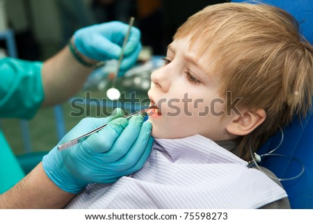 Close-up of little boy opening his mouth wide during inspection of oral cavity - stock photo