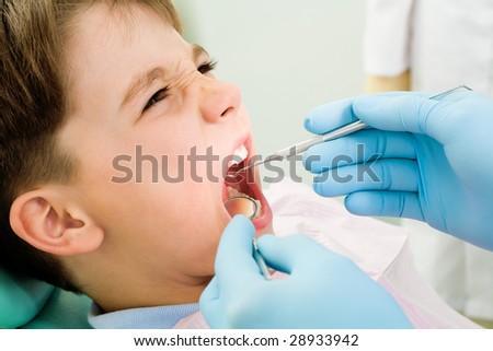 Close-up of little boy opening mouth for dental checkup in stomatological office - stock photo